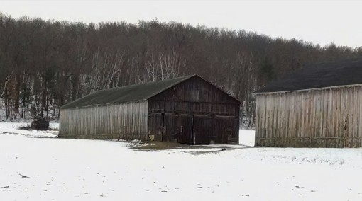 A weathered tobacco barn in the snow